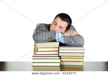 Business man sleeping on book heaps isolated on white