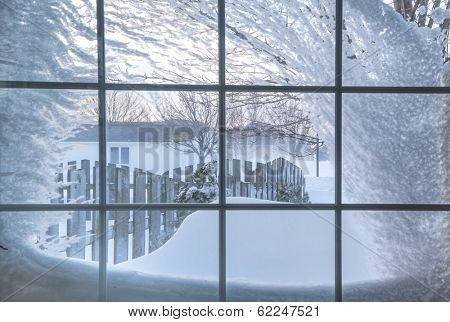 Snow covered window with a view out into a residential neighborhood.