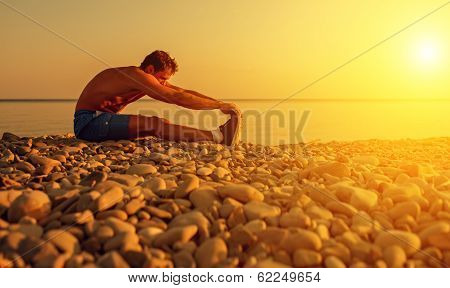 Athlete Practicing, Playing Sports And Yoga On The Beach At Sunset