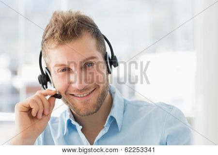 Smiling call centre agent wearing a headset in creative office