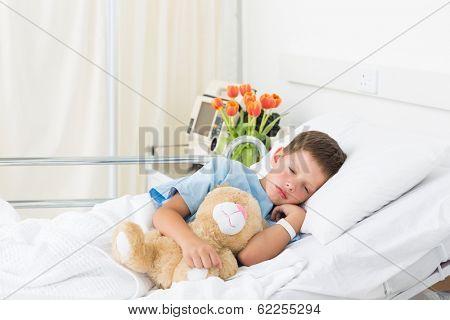 Sick little boy sleeping with teddy bear in hospital bed