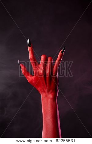 Red devil hand showing heavy metal gesture, studio shot on smoky background