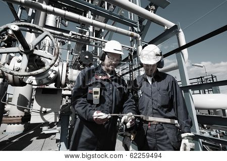 oil and gas workers inside large petrochemical oil refinery