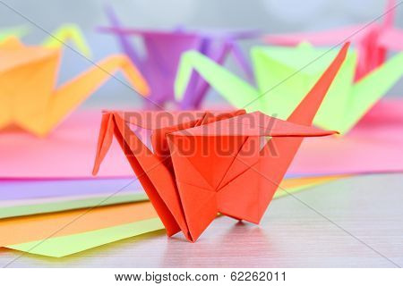 Origami cranes on wooden table, on light background