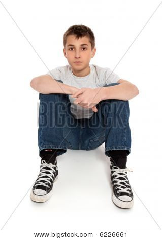 Pre Teen Boy Sitting In Jeans And T-shirt