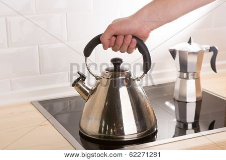 Tea Kettle In Hand On Black Stove