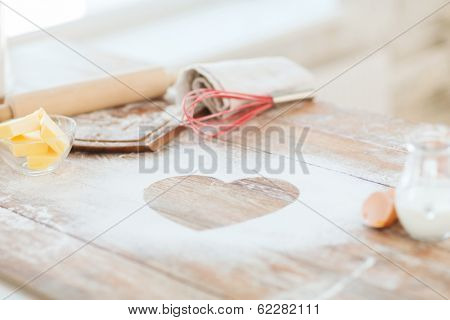 cooking and love concept - close up of heart of flour on wooden table at home