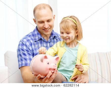family, children, money, investment and happy people concept - happy father and daughter with big pink piggy bank