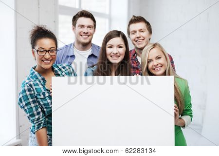 education concept - group of students at school with blank white board