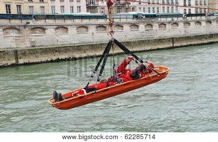 PARIS, FRANCE - MARCH 18, 2014: Firefighters of the elite GRIMP unit carry out a training exercise at the Pont Saint Michel on the River Seine. The unit specialises in rescues in hazardous situations.