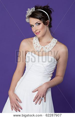 Beautiful young bride wearing white dress and white lace collar with flower band on purple studio background