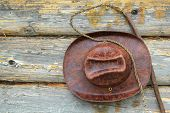 stock photo of whipping  - Leather hat and whip hanging on the wall of a wooden house - JPG