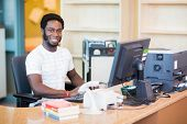 picture of librarian  - Portrait of confident male librarian working at desk in library - JPG