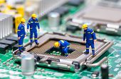 stock photo of figurine  - Group of construction workers repairing CPU - JPG