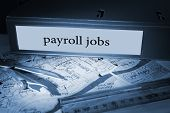 picture of payroll  - The word payroll jobs on blue business binder on a desk - JPG
