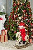 Little smiling girl dressed in santa suit rocks on rocking horse under Christmas tree on furry rug poster
