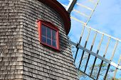 picture of red siding  - weathered siding with a red trimmed window looking upward at the windmill vanes - JPG