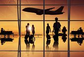 stock photo of leaving  - Silhouette of Travellers and Pilot at an Airport - JPG