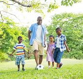 picture of pre-adolescent child  - African Father Playing Ball with Children in Park - JPG