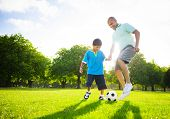 stock photo of pre-adolescents  - Father and Son Playing Ball in The Park - JPG