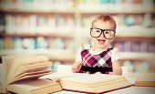 stock photo of schoolgirls  - funny baby girl in glasses reading a book in a library - JPG