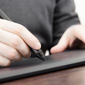 foto of scribes  - Man working on professional graphic tablet with pen  - JPG