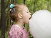 image of candy cotton  - Young caucasian little girl eating big white cotton candy in the park outdoor - JPG
