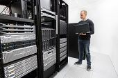 stock photo of racks  - It engineer or consultant standing with a laptop and monitor blade servers in data rack - JPG
