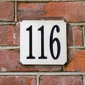 picture of formica  - house number one hundred and sixteen engraved in a white formica plate - JPG