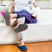 pic of pajamas  - Married couple reading newspaper dressed in pajamas sitting in sofa at home - JPG