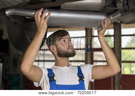Male Car Mechanic Changing Car Exhaust