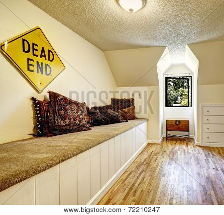 Bench With Carpet Cover And Brown Pillows In Empty Room