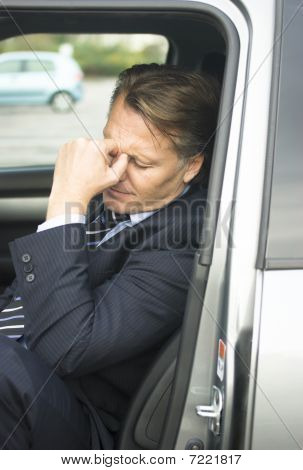 A tired stressed businessman in car