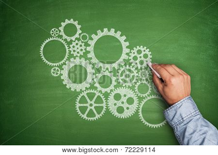 Cogwheels concept on blackboard