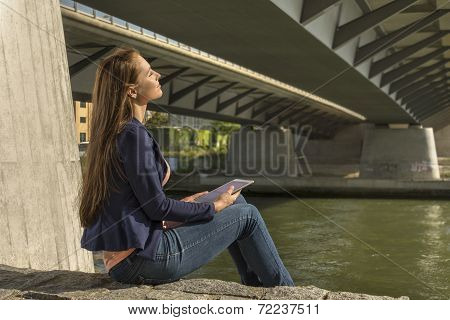 Pretty Young Woman Relaxing At Urban Riverside