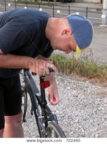 Cyclist Adjusting The Saddle