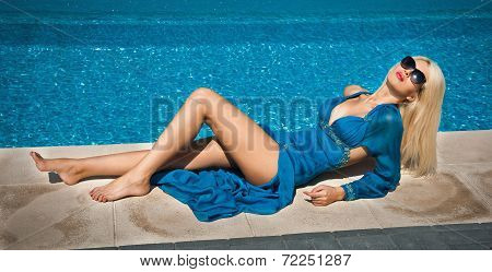 Beautiful sensual blonde with fashionable sun glasses relaxing at the pool
