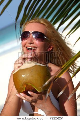 Beautiful Blondy Holding Coconut In Tropical Beach