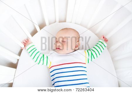 Cute Newborn Little Boy Sleeping In A White Round Crib