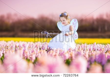 Toddler Girl In Fairy Costume Playing In A Flower Field