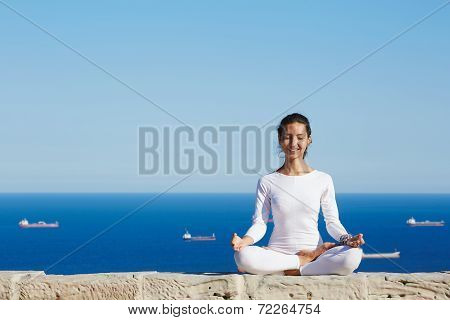 Attractive brunette girl smiling seated in yoga pose on beautiful sea background, healthy woman smil