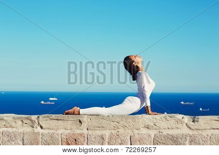 Beautiful woman in white clothes seated in yoga pose on blue sea background, healthy young woman med