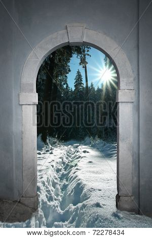 View Through Arched Gate To Wintry Forest With Bright Sunshine