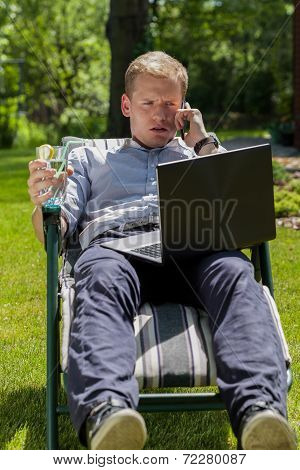 Businessman Talking On Phone In Garden