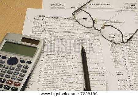 Formularios de impuestos con calculadora, gafas y pluma