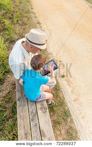 Grandchild and grandfather using a tablet outdoors