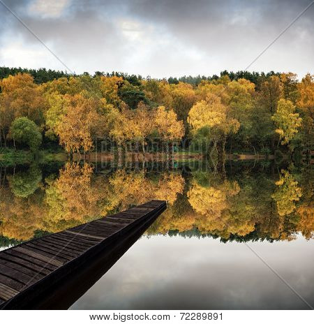 Beautiful Vibrant Autumn Woodland Reflecions In Calm Lake Waters Landscape