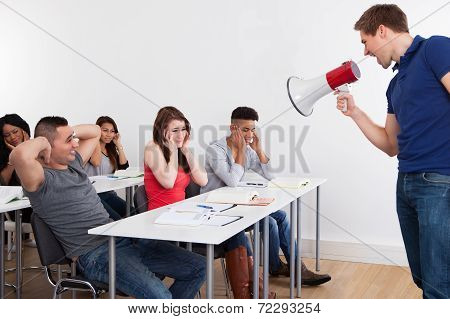 Teacher Shouting Through Megaphone On University Students