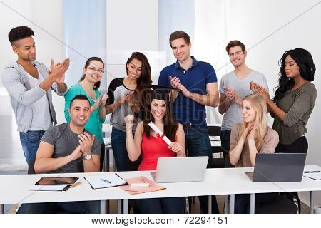 Students Clapping For Classmate Holding Degree