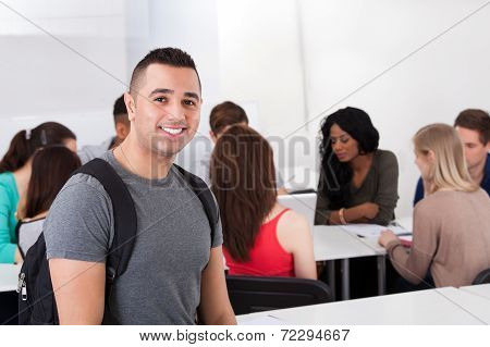 Confident Male Student Carrying Backpack In Classroom